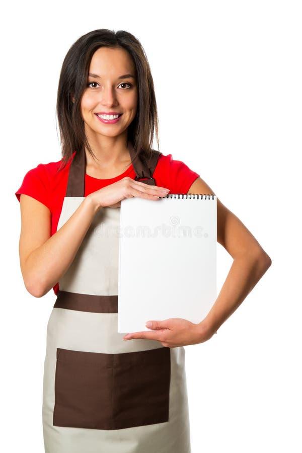 Кашевар женщины в шляпе шеф-повара с пустой доской, на белизне стоковые изображения