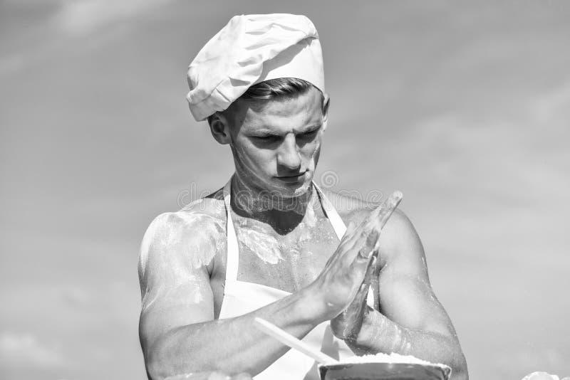 Кашевар или шеф-повар с сексуальными мышечными плечами и комод покрытый с мукой Кашевар шеф-повара подготавливая тесто для печь с стоковые фотографии rf