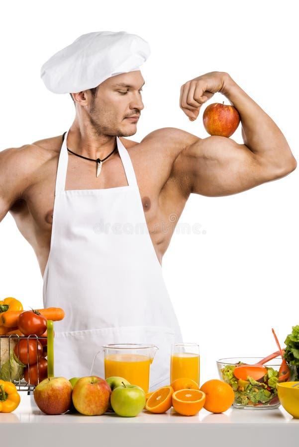Кашевар культуриста человека с яблоком на бицепсе стоковые фотографии rf