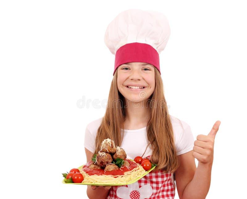 Кашевар маленькой девочки с спагетти и фрикадельками и большим пальцем руки вверх стоковое изображение rf