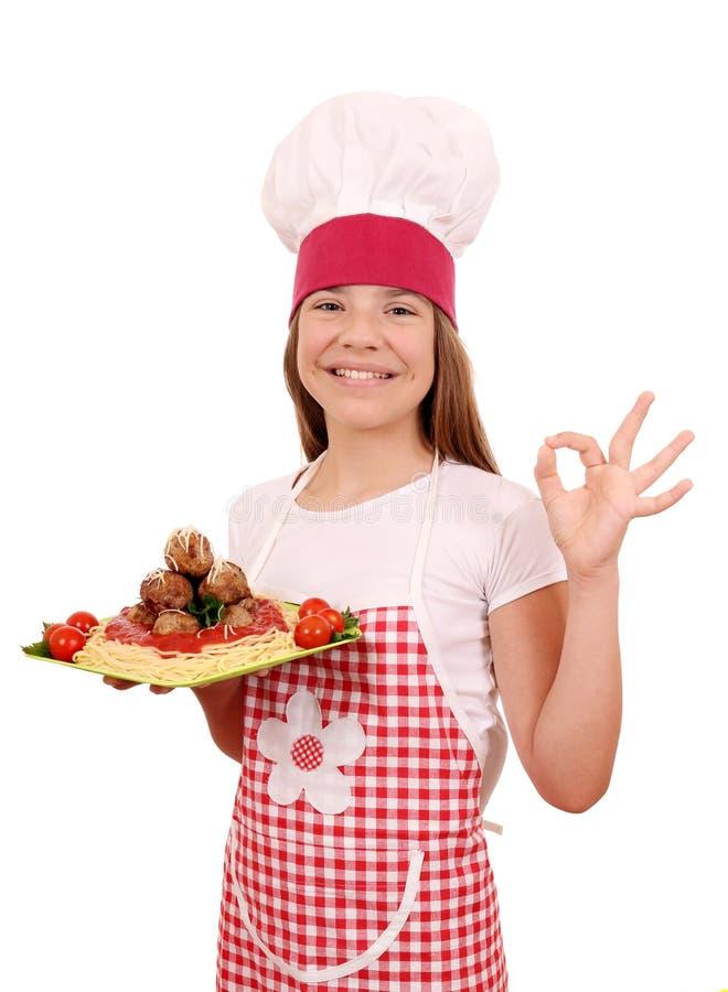 Кашевар маленькой девочки с спагетти и фрикадельками и одобренной рукой стоковое фото