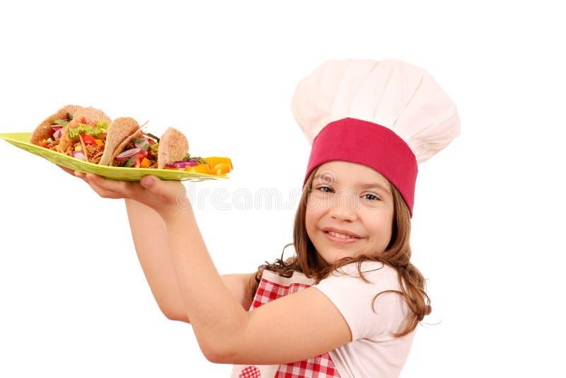 Кашевар маленькой девочки с тако стоковое изображение rf