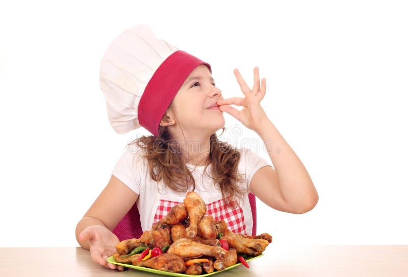 Кашевар маленькой девочки с drumstick цыпленка и одобренная рука подписывают стоковая фотография rf