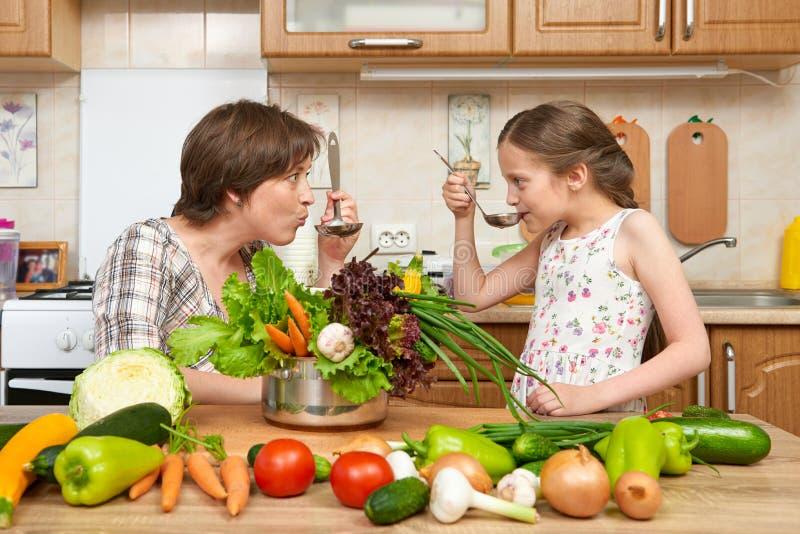 Кашевар матери и дочери и суп вкуса от овощей Домашний интерьер кухни Родитель и ребенок, женщина и девушка Здоровый жулик еды стоковое фото