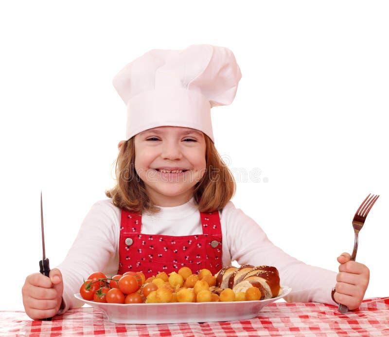 Кашевар маленькой девочки ест еду лакомки стоковые фото