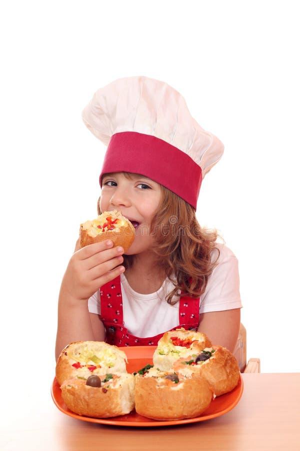 Кашевар маленькой девочки ест хлеб заполненный с сыром стоковые фото