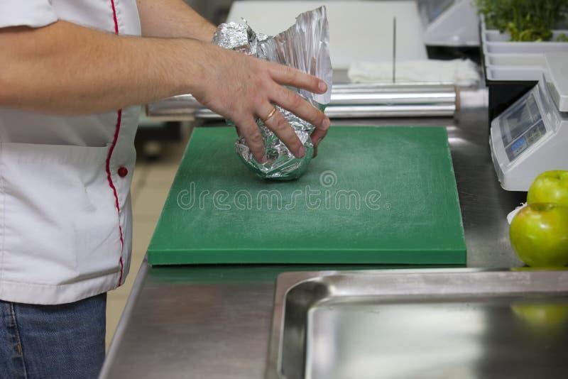 Кашевар оборачивает яблоко в фольге стоковая фотография rf