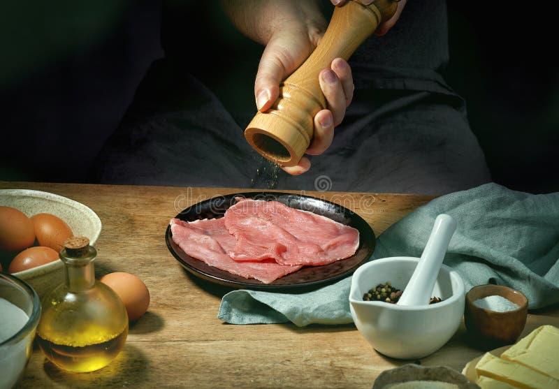 Кашевар приправляет мясо стоковые изображения rf