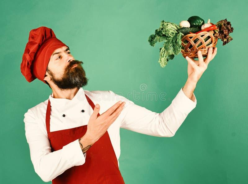 Кашевар с гордой стороной в бургундской форме представляет овощи стоковые изображения