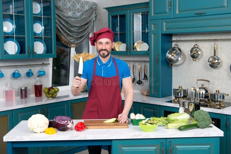 Кашевар с ножом и доска Гай на кухне держит нож в руке Оружие ` s человека для обедающего стоковое фото