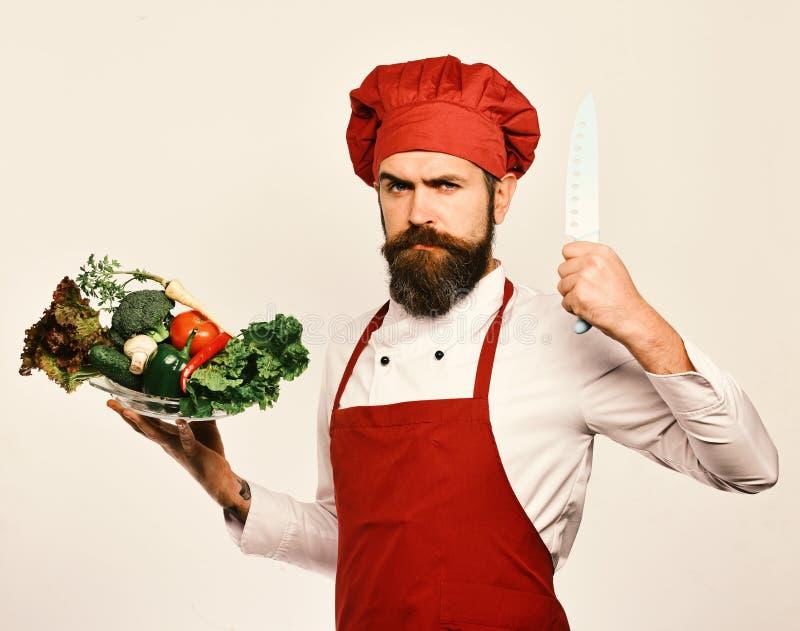 Кашевар с серьезной стороной в бургундской форме держит ингридиенты салата стоковые изображения rf