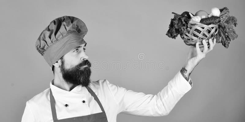 Кашевар с спокойной стороной в бургундской форме смотрит овощи стоковые фото