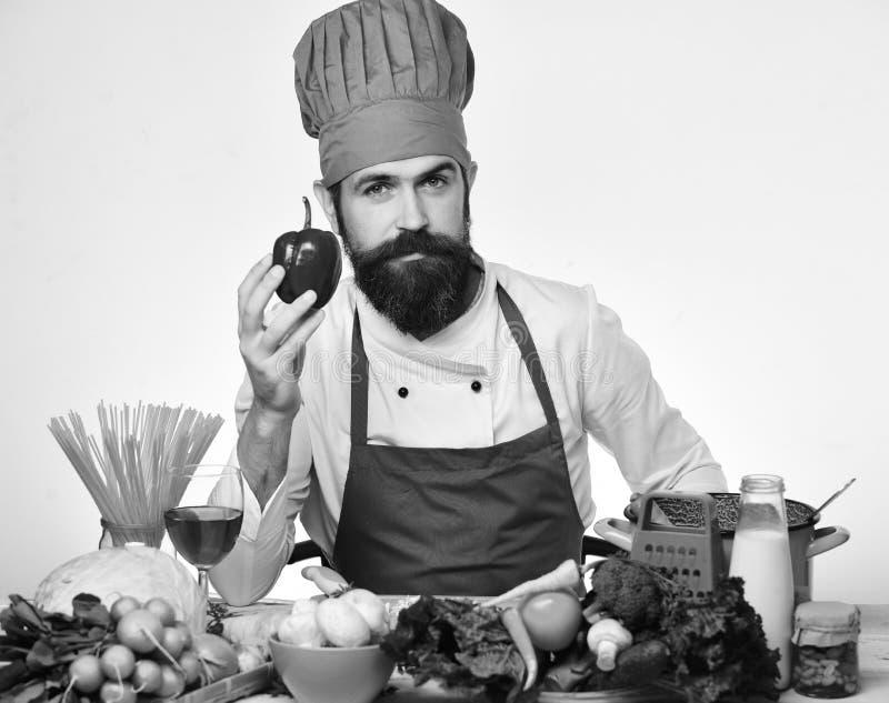 Кашевар с спокойной стороной в форме сидит кухонным столом стоковая фотография