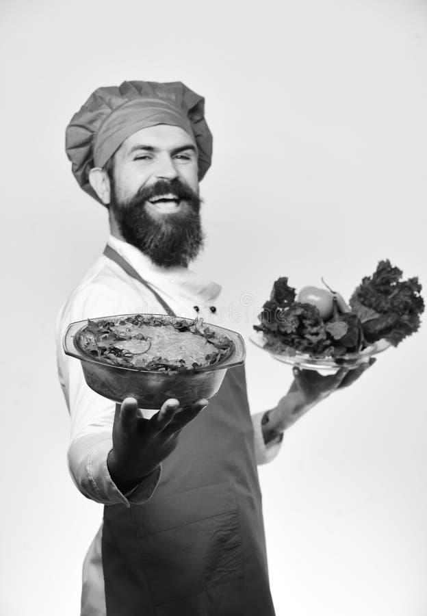 Кашевар с стороной улыбки в бургундской форме держит испеченное блюдо стоковое изображение rf