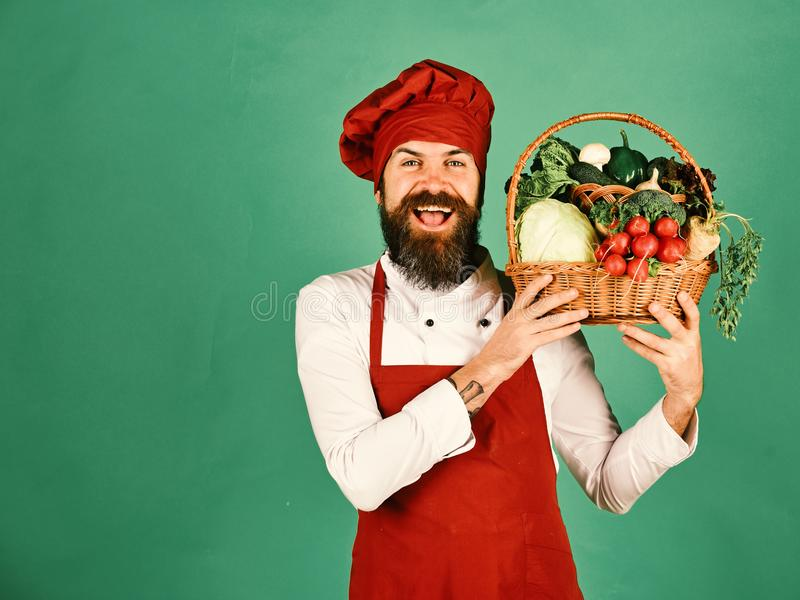 Кашевар с счастливой стороной в бургундской форме держит овощи в корзине Концепция зеленой бакалеи Шеф-повар держит капусту, реди стоковое изображение rf