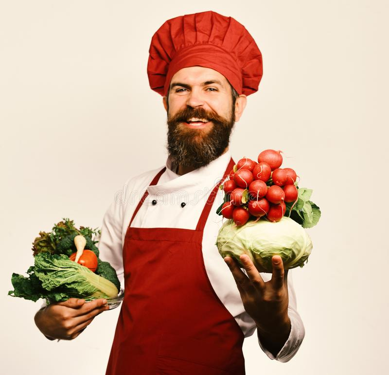 Кашевар с счастливой стороной в форме держит капусту и редиску стоковое фото