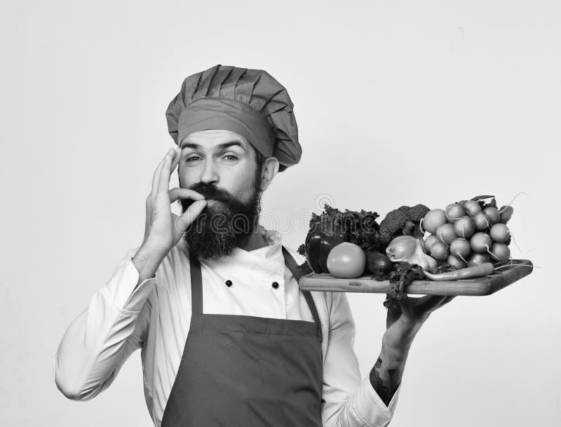 Кашевар с удовлетворенной стороной в бургундской форме держит ингридиенты салата стоковая фотография