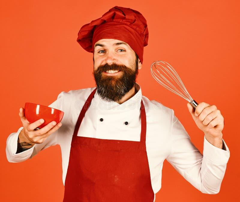 Кашевар с excited стороной в бургундской шляпе и рисберме держит шар и юркнет Шеф-повар с красными плитой и взбивать утварью Чело стоковое фото rf
