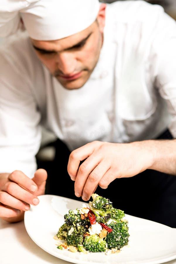 Кашевар украшая салат брокколи стоковые фото