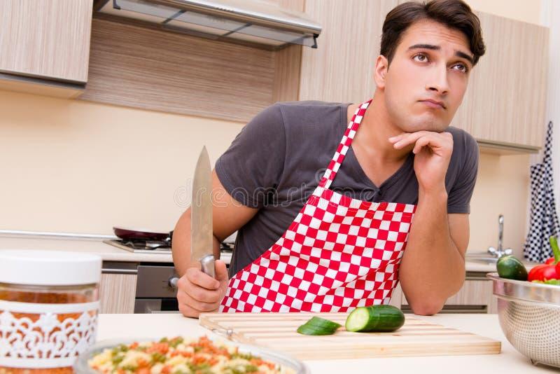 Кашевар человека мужской подготавливая еду в кухне стоковые фото