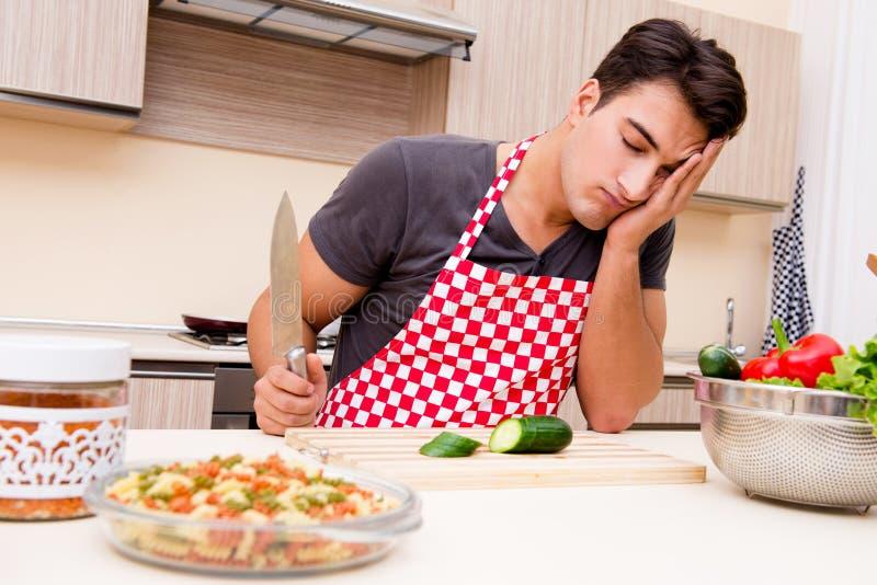 Кашевар человека мужской подготавливая еду в кухне стоковое фото