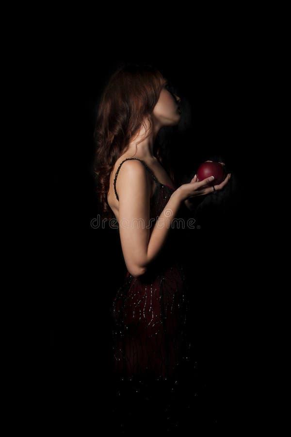 Каштановая с волосами женщина при, который подвергли действию шея держа яблоко в руке стоковые изображения