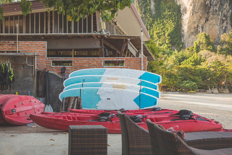 Каяки и плавая доски на песчаном пляже рано утром Спасательные жилеты висят к левой стороне Аренда оборудования водных видов спор стоковое фото