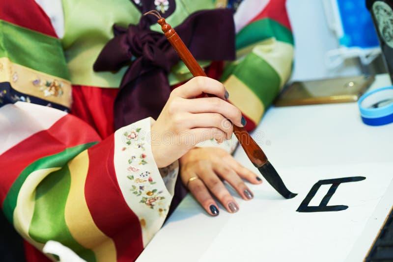 каллиграфия Женская рука писать корейский иероглиф стоковое изображение rf