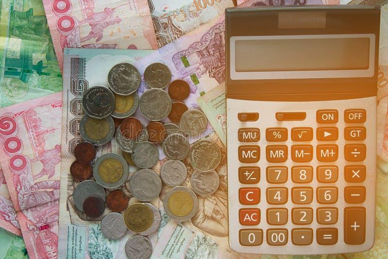 Калькулятор на банкнотах и монетках денег тайского бата стоковые изображения