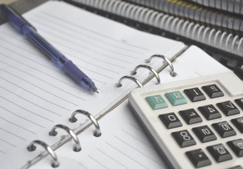 Калькулятор на тетради с ручкой стоковая фотография rf