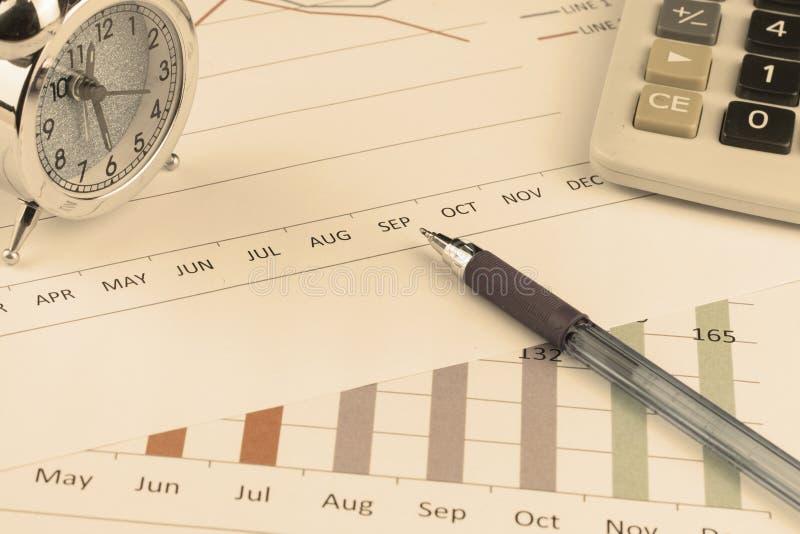 Калькулятор, ручка и будильник на предпосылке диаграммы стоковая фотография