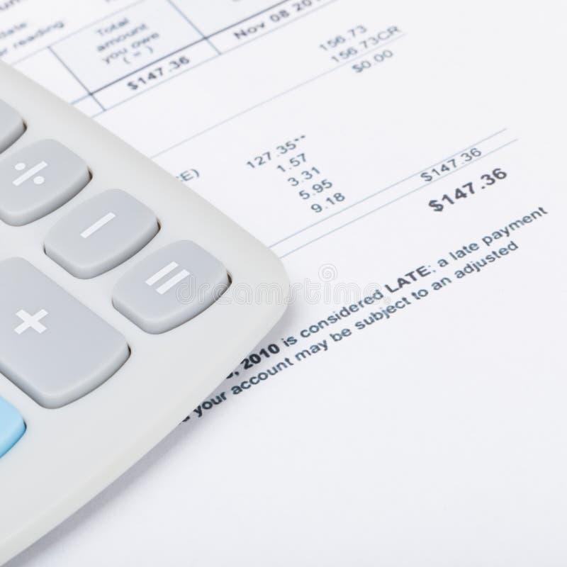 Калькулятор с счетами за коммунальные услуги под им - близкая поднимающая вверх съемка студии стоковые фотографии rf