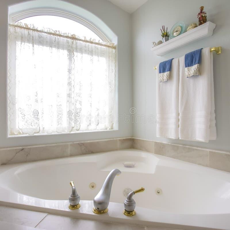 Квадратная ванна рамки с с золотом и серебряным faucet около сдобренного окна с занавесом стоковые изображения rf