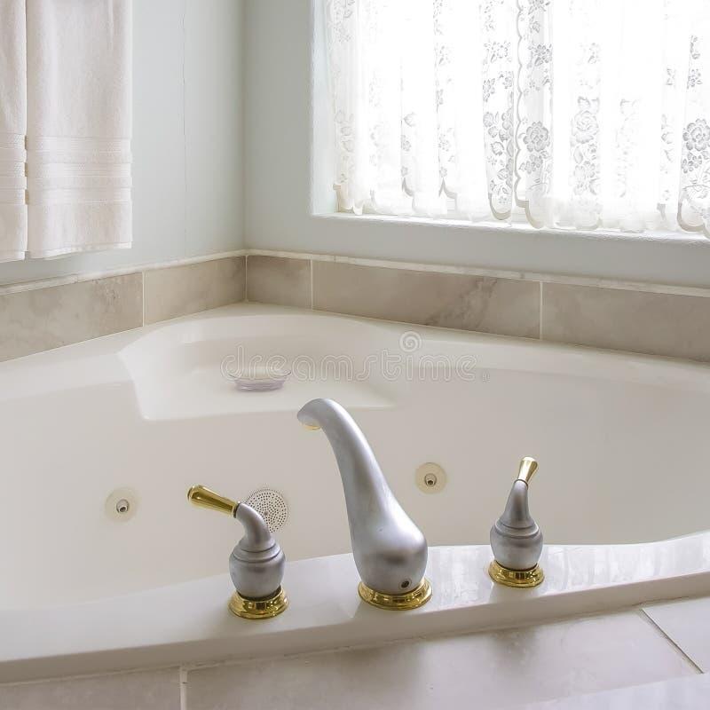 Квадратная ванна с с золотом и серебряным faucet около сдобренного окна с занавесом стоковые фото