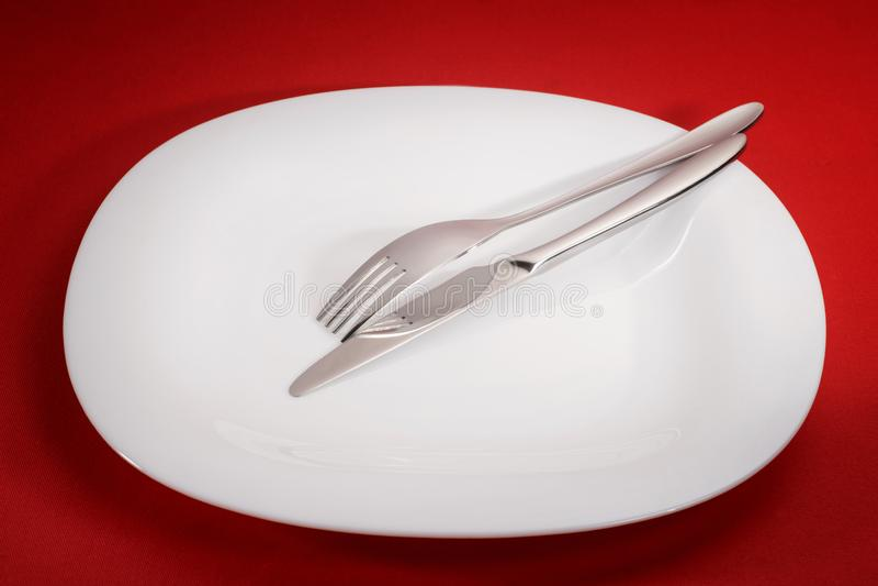 Квадратная плита с вилкой и нож на красном цвете стоковые фотографии rf