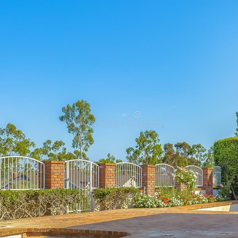 Квадратное патио кирпича рамки с поднятой платформой перед сдобренными белыми воротами стоковое фото