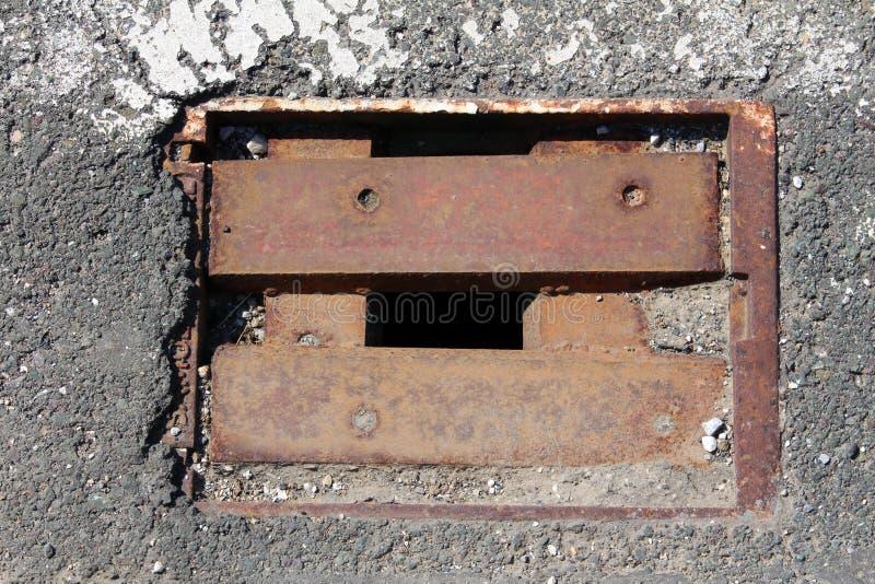 Квадрат заржавел железное отверстие стока при пропуская крышка решеток окруженная с треснутым асфальтом стоковые фото