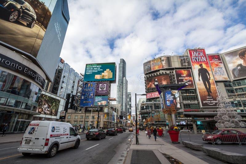 Квадрат Yonge Dundas, с людьми и автомобилями пересекая на тротуар, окруженный небоскребами, торговыми центрами, магазинами и маг стоковая фотография rf