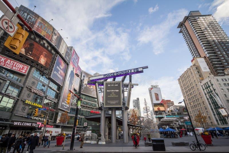 Квадрат Yonge Dundas, с людьми и автомобилями пересекая на тротуар, окруженный небоскребами, торговыми центрами, магазинами и маг стоковые фотографии rf