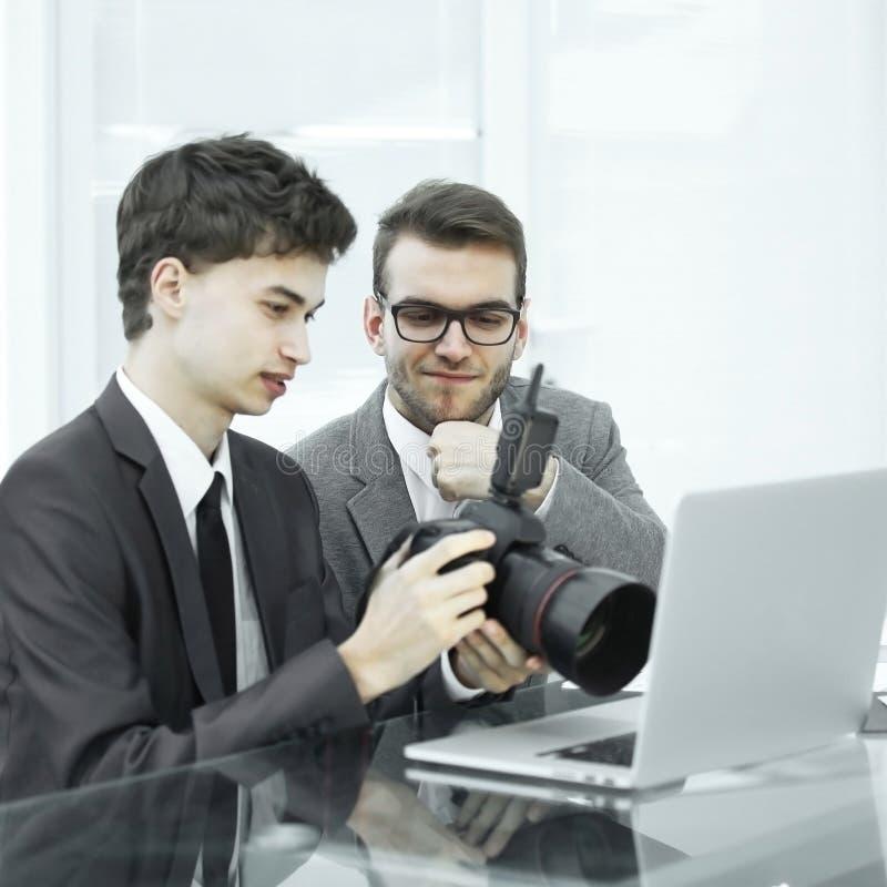 Квалифицированные фотографы выбирают фото для того чтобы загружать файлы к их компьтер-книжкам стоковая фотография rf