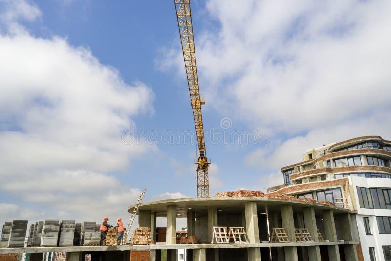 Квартира или высотное здание офиса под конструкцией Кирпичные стены, окна стекла, леса и конкретные штендеры поддержки Башня стоковое фото