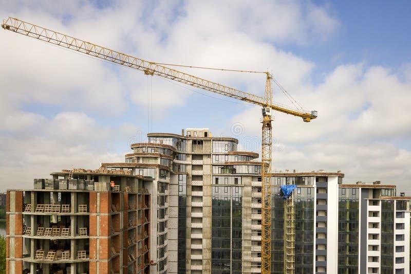 Квартира или высотное здание офиса под конструкцией Кирпичные стены, окна стекла, леса и конкретные штендеры поддержки Башня стоковые фото