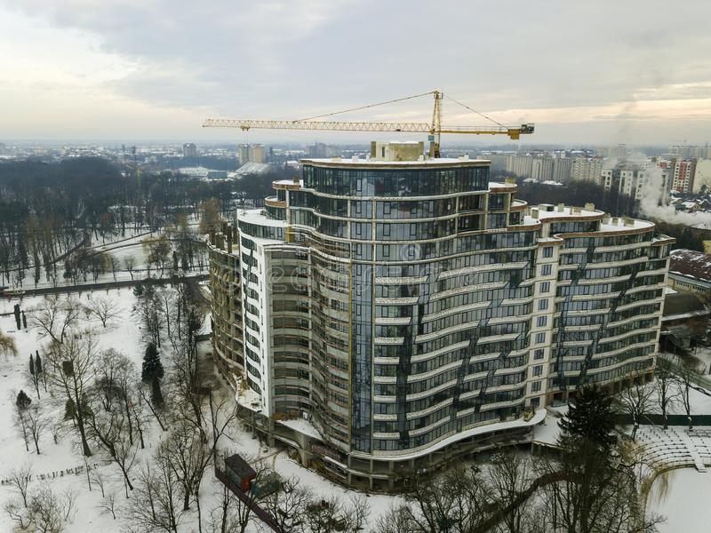 Квартира или офисное здание под конструкцией, видом с воздуха Силуэт крана башни на предпосылке космоса экземпляра голубого неба стоковая фотография