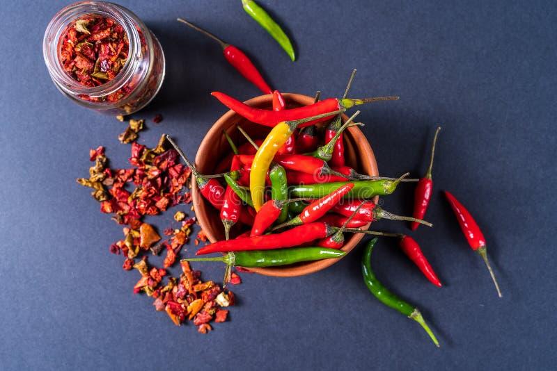 Квартира кладет красные, зеленые и желтые перцы chili в шаре и специи paprica над серой предпосылкой стоковые фотографии rf