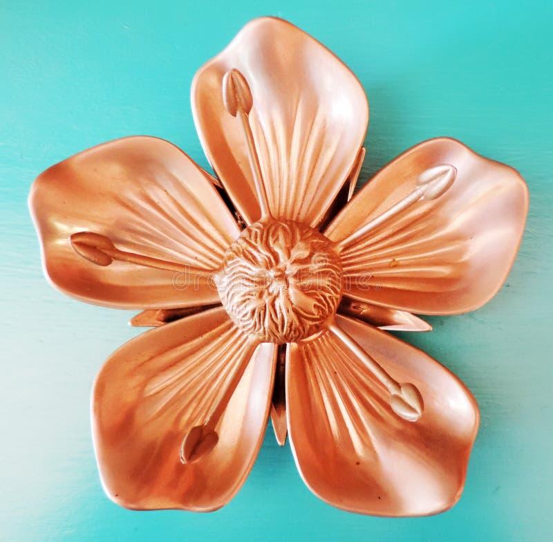 Квадратный бронзовый орнамент цветка металла на предпосылке бирюзы стоковая фотография