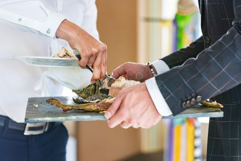 Кельнер вручает стерляжину испеченную вырезыванием в ресторане стоковое фото