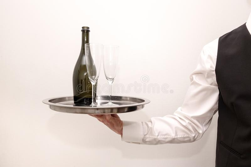 Кельнер/дворецкий нося серебряный поднос с бутылкой шампанского стоковые фото