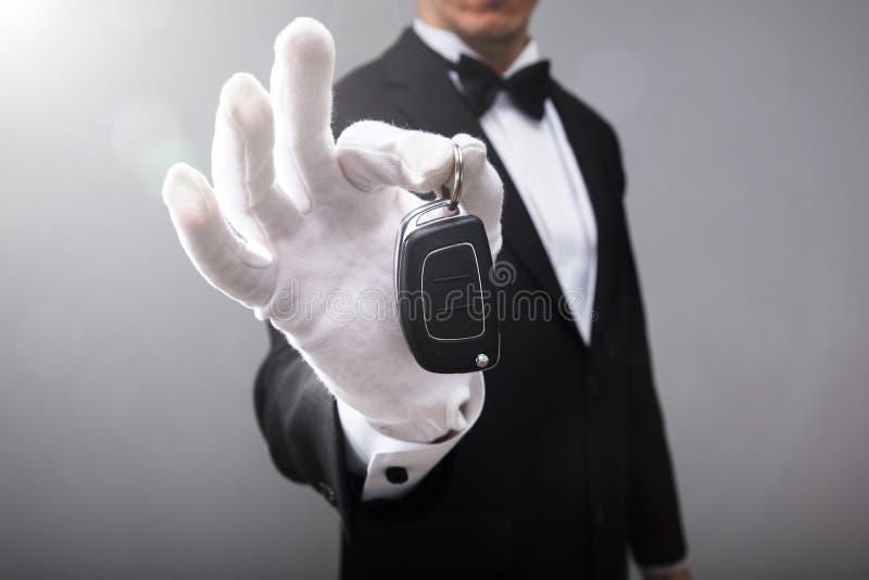 Кельнер держа ключ автомобиля стоковые фото