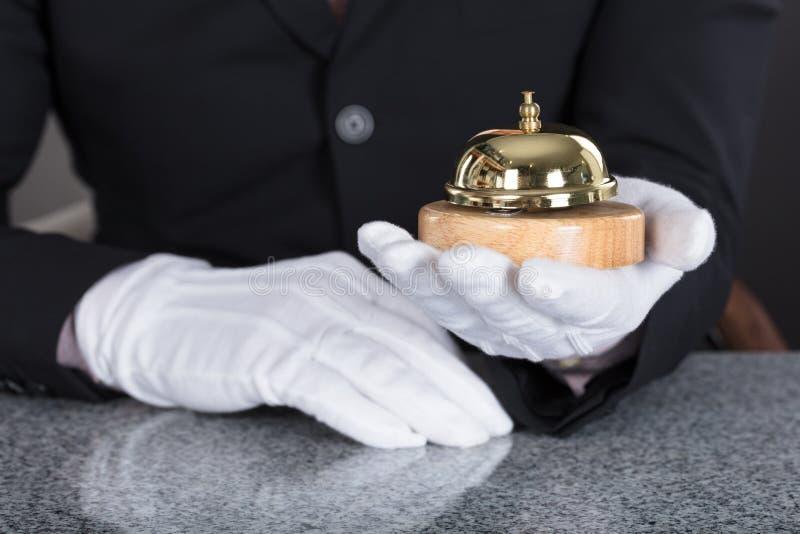 Кельнер держа обслуживание колокол стоковое изображение
