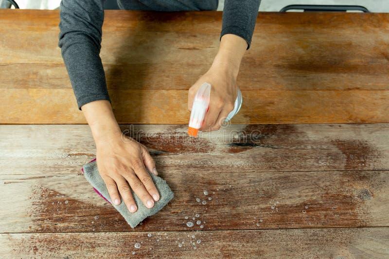 Кельнер очищая таблицу с дезинфектантом брызга в кафе стоковая фотография rf